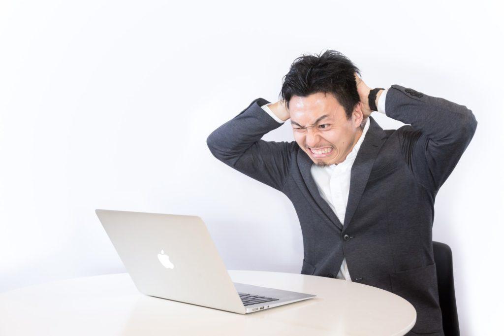 ノートパソコンの前で頭を抱える男性