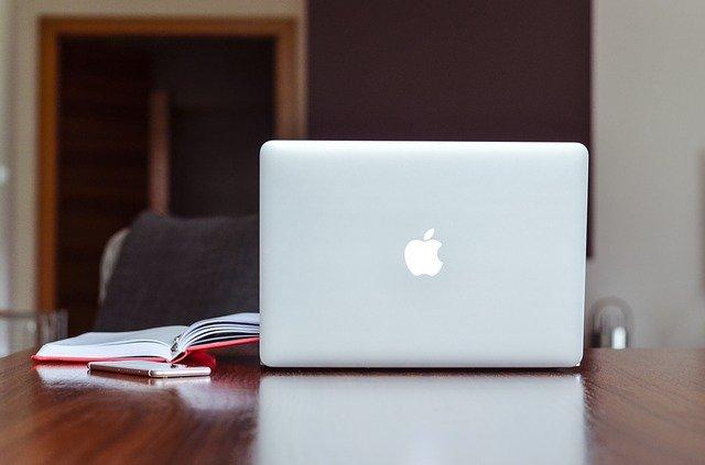Appleのパソコンと本が載った机と椅子