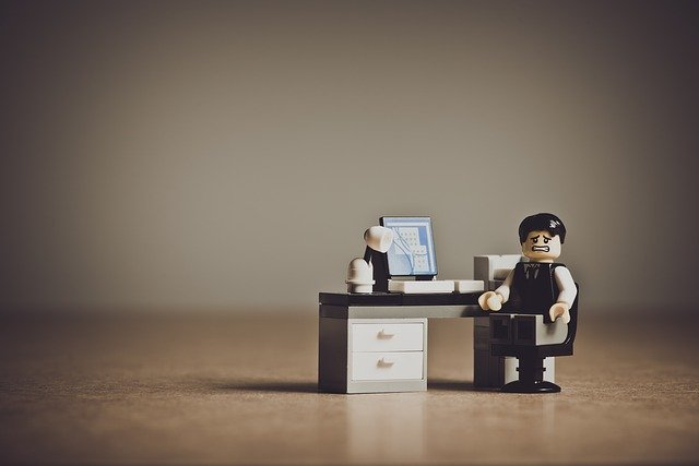 パソコンを置いた机に向かう、難しい顔をした男性のレゴ
