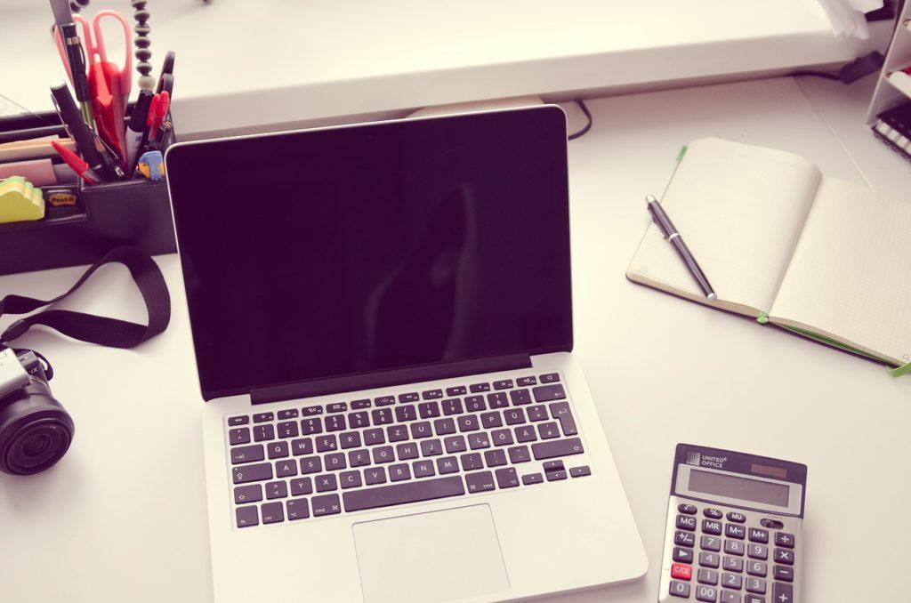 ノートパソコンと電卓と開いたノートの画像