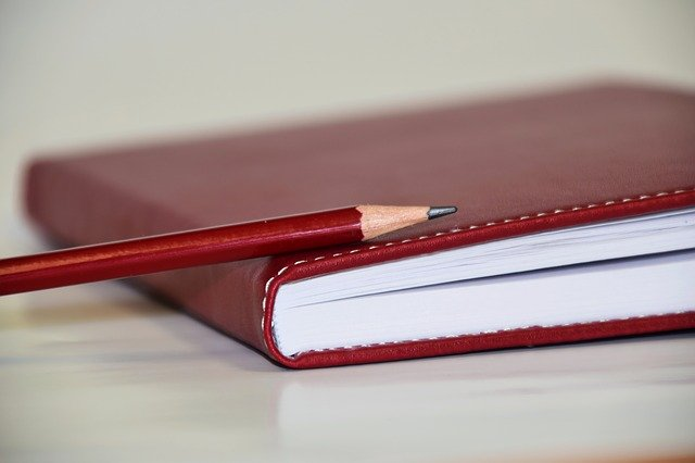 名簿と鉛筆が映った画像