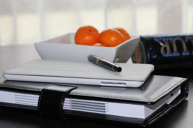 名簿とスマホとペンが机に載った画像