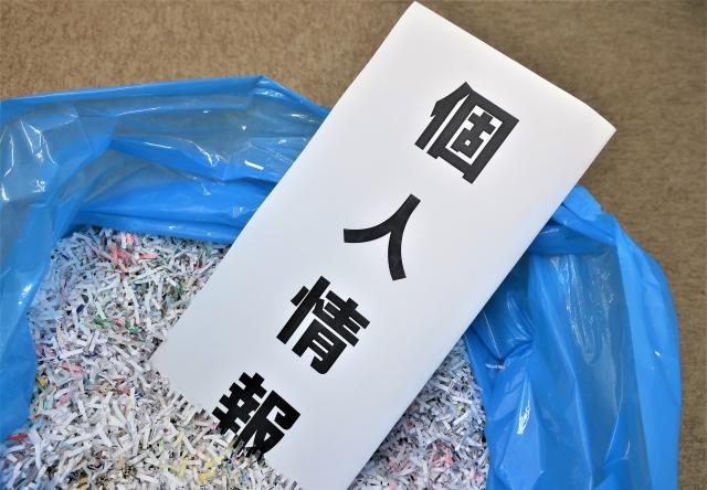 個人情報と書かれた紙がシュレッダーにかけられたゴミに埋まっている画像